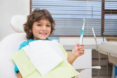 Rapaz pequeno na cadeira dos dentistas que guarda o toothrbrush fotos de stock royalty free