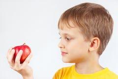 Rapaz pequeno na camisa amarela com maçã vermelha fotos de stock royalty free