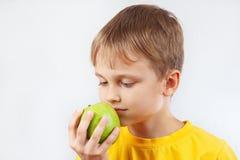Rapaz pequeno na camisa amarela com uma maçã verde foto de stock royalty free