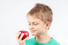 Rapaz pequeno na camisa verde com maçã vermelha Imagens de Stock