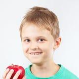 Rapaz pequeno na camisa verde com a maçã vermelha madura Foto de Stock Royalty Free