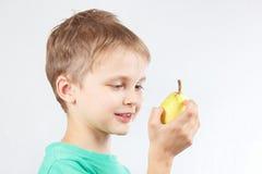 Rapaz pequeno na camisa verde com pera amarela Imagens de Stock