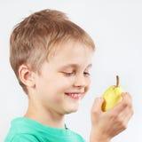 Rapaz pequeno na camisa verde com a pera amarela madura Fotos de Stock Royalty Free