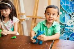 Rapaz pequeno na classe da escultura fotografia de stock