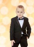 Rapaz pequeno na moda em um terno preto com um laço Fotografia de Stock Royalty Free