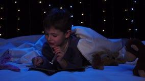 Rapaz pequeno na noite que lê um livro na cama Fundo de Bokeh filme