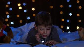 Rapaz pequeno na noite que lê um livro na cama Fundo de Bokeh video estoque