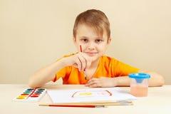 Rapaz pequeno na pintura alaranjada da camisa com aquarelas foto de stock