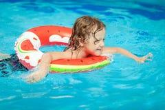 Rapaz pequeno na piscina com anel de borracha imagens de stock royalty free