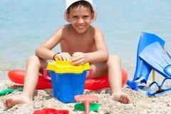 Rapaz pequeno na praia tropical que joga na areia Imagem de Stock