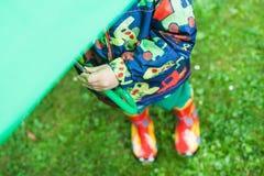Rapaz pequeno na roupa e nas botas da chuva que escondem sob o guarda-chuva verde Fotografia de Stock Royalty Free