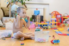 Rapaz pequeno na sala de jogos com brinquedos Sala completamente dos brinquedos Lotes dos brinquedos, muitos carros empilhados no fotos de stock