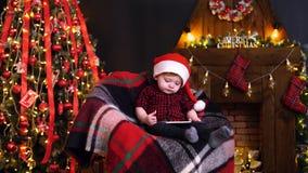 Rapaz pequeno nas decorações do Natal que jogam o smartphone filme