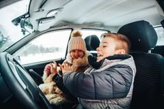 Rapaz pequeno no carro como um motorista e uma menina pequena perto dela como um passanger imagens de stock royalty free