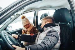 Rapaz pequeno no carro como um motorista e uma menina pequena perto dela como um passanger imagem de stock