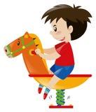 Rapaz pequeno no cavalo de balanço Foto de Stock Royalty Free