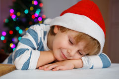 Rapaz pequeno no chapéu de Santa com árvore e luzes de Natal Fotos de Stock Royalty Free