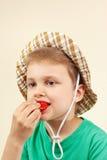 Rapaz pequeno no chapéu do verão que come a morango madura fresca Foto de Stock Royalty Free