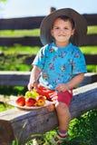Rapaz pequeno no chapéu engraçado com frutas Foto de Stock