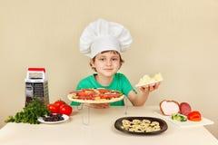 Rapaz pequeno no chapéu dos cozinheiros chefe com queijo raspado para a pizza Imagens de Stock Royalty Free