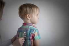 Rapaz pequeno no doutor, estetoscópio de utilização fêmea Fotografia de Stock Royalty Free