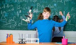 Rapaz pequeno no laboratório Ciência da química experiências da biologia com microscópio Crianças que ganham a química no laborat fotografia de stock