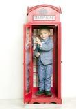 Rapaz pequeno no telefone vermelho inglês Imagens de Stock