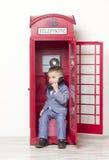 Rapaz pequeno no telefone vermelho inglês Fotos de Stock