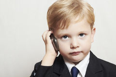Rapaz pequeno no terno de negócio com telefone celular. criança considerável. criança elegante Fotografia de Stock Royalty Free