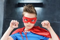rapaz pequeno no traje vermelho do super-herói que gesticula e que olha fotografia de stock