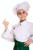 Rapaz pequeno no uniforme do cozinheiro chefe com aprovação Foto de Stock Royalty Free