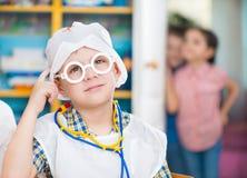 Rapaz pequeno no uniforme médico que joga no doutor Foto de Stock