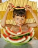 Rapaz pequeno novo bonito com crustes da melancia Imagem de Stock