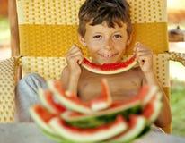 Rapaz pequeno novo bonito com crustes da melancia Imagens de Stock Royalty Free