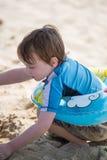 Rapaz pequeno novo que joga com a areia e o castelo de areia de construção na praia perto da baía Imagem de Stock