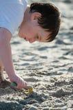 Rapaz pequeno novo que joga com a areia e o castelo de areia de construção na praia perto do mar Foto de Stock
