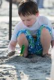 Rapaz pequeno novo que joga com a areia e o castelo de areia de construção na praia perto do mar Imagem de Stock