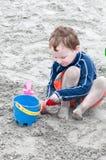 Rapaz pequeno novo que joga com a areia e o castelo de areia de construção na praia perto do mar Imagens de Stock Royalty Free