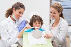 A rapaz pequeno pediatra do dentista mostrando como escovar os dentes com sua mãe fotografia de stock royalty free
