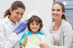 A rapaz pequeno pediatra do dentista mostrando como escovar os dentes com sua mãe foto de stock