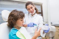 A rapaz pequeno pediatra do dentista mostrando como escovar seus dentes imagem de stock royalty free