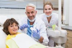A rapaz pequeno pediatra do dentista mostrando como escovar seus dentes imagem de stock