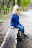 Rapaz pequeno pensativo pensativo que senta-se em um banco de madeira em uma paridade Imagens de Stock Royalty Free