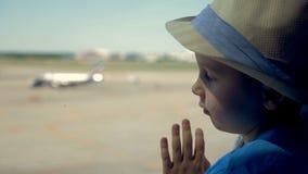 Rapaz pequeno perto da janela, fim acima Um menino olha através da janela grande em planos em uma pista de decolagem filme