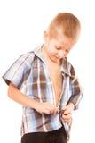 Rapaz pequeno que abotoa-se na camisa, isolada no branco fotografia de stock royalty free