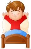 Rapaz pequeno que acorda em uma cama no fundo branco Fotos de Stock