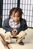 Rapaz pequeno que agacha-se imagem de stock