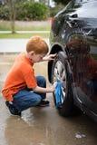 Rapaz pequeno que ajuda a lavagem o carro do seu pai imagens de stock royalty free