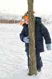 Rapaz pequeno que amua e que esconde atrás de um tronco de árvore Imagens de Stock Royalty Free