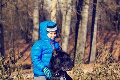 Rapaz pequeno que anda com cão grande Foto de Stock Royalty Free